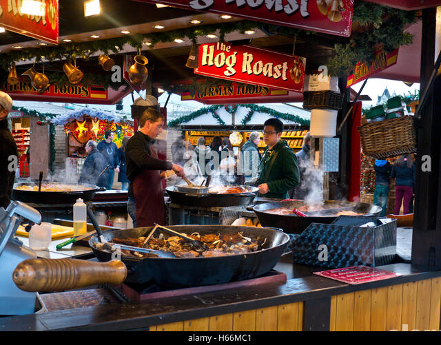 CHRISTMAS HOT WINTER FOOD STALL MARKET South Bank German Christmas market takeaway hog roast food stall and visitors - Stock Image