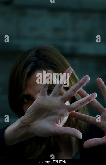 Woman raising hands to ward off attack - Stock Image