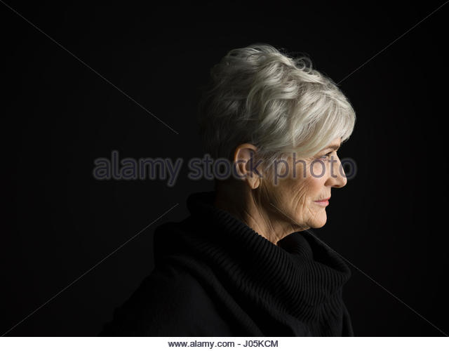 Profile portrait senior woman with short gray hair looking away against black background - Stock Image