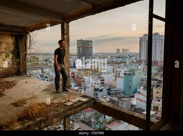 Man standing in derelict building looking at city, Ho Chi Minh, Vietnam - Stock-Bilder