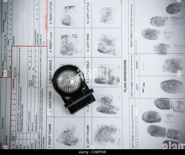 Loupe over fingerprints on arrest form - Stock Image