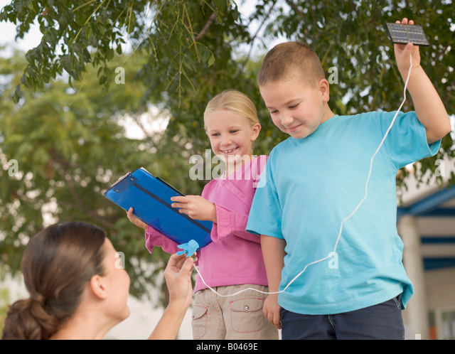 Children holding solar panels - Stock Image