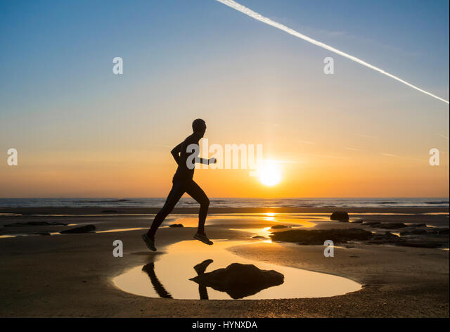 Seaton Carew, County Durham, UK. 6th Apr, 2017. Weather: A jogger on Seaton Carew beach at sunrise on a glorious - Stock Image