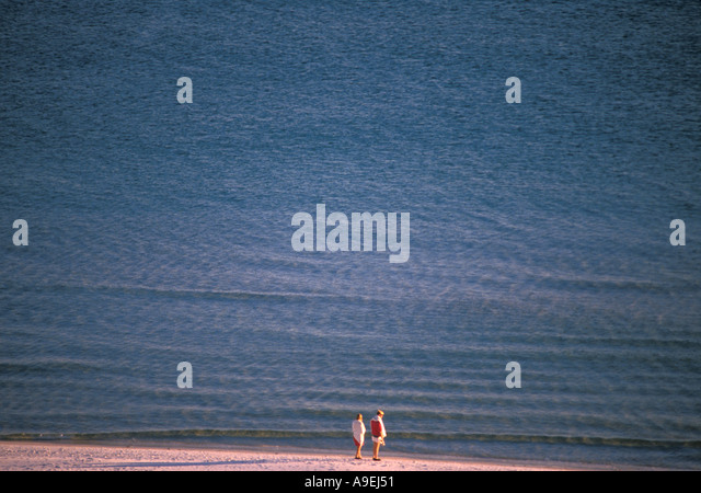 Couple walking on beach in late afternoon calm water seen from a distance - Stock Image