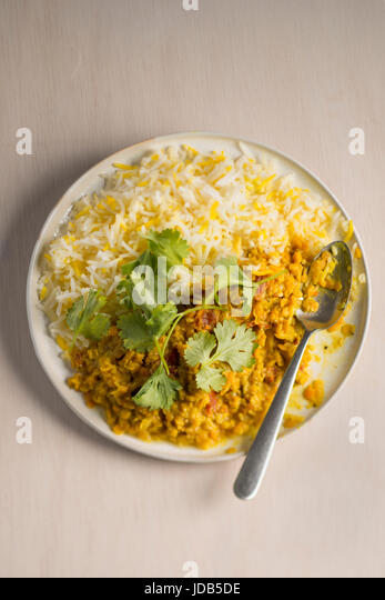 One plate of vegan lentil curry with basmati rice, topped with fresh coriander leaves,  on a light wooden background - Stock Image