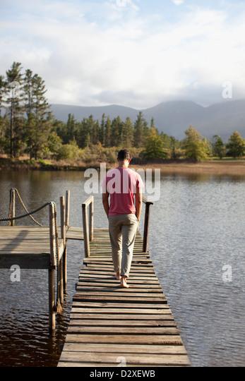 Man walking along dock over lake - Stock Image