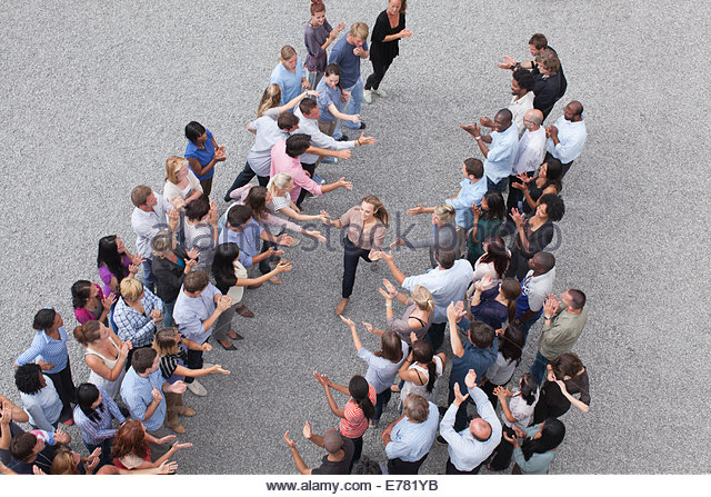 Woman walking past crowd, high-fiving people - Stock-Bilder