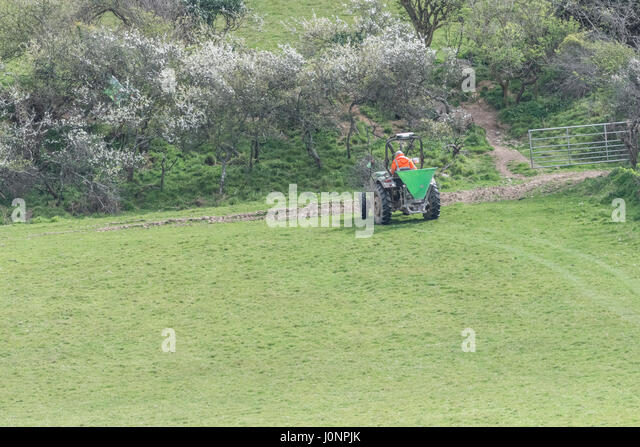 Distant shot of farm tractor with top dresser. Metaphor for food security / growing food. - Stock Image