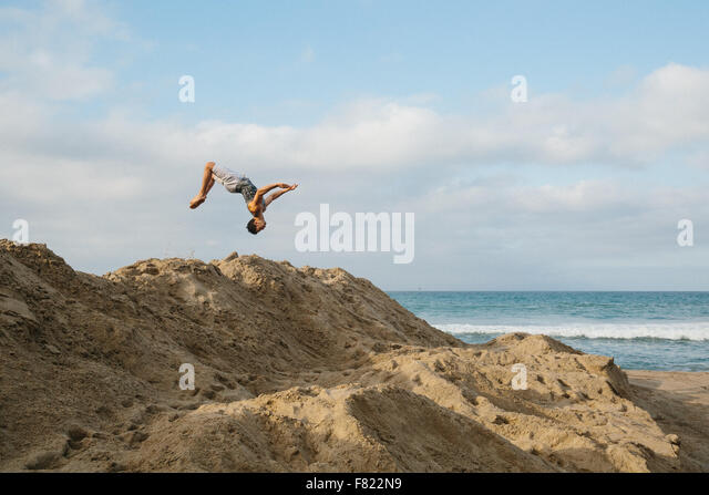 A young man flips over sand dunes on a beach in California - Stock Image