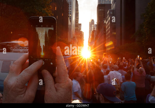 New York, USA. 11th July, 2016. A man takes photo of Manhattanhenge with his iPhone in Manhattan, New York, the - Stock Image
