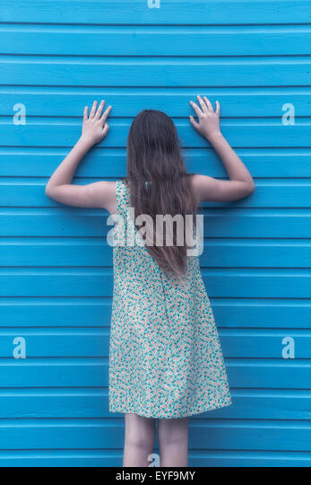 a girl with a floral dress is leaning against a wooden wall - Stock Image