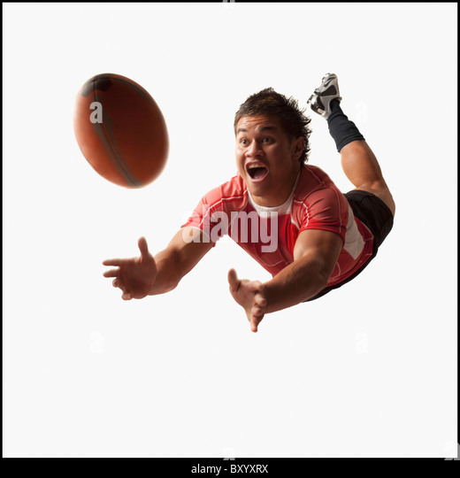 Male rugby player diving for ball - Stock Image