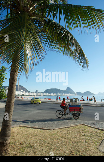 RIO DE JANEIRO, BRAZIL - FEBRUARY 03, 2014: Brazilian man delivering cooler and chairs to beach kiosk on a tricycle - Stock Image
