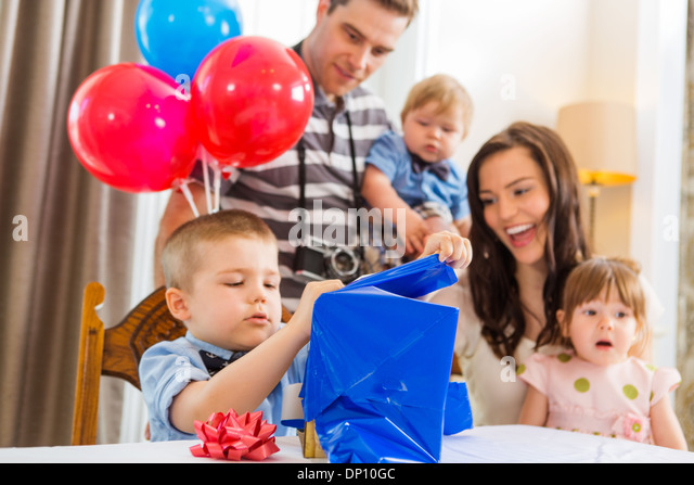 Family Looking At Birthday Boy Opening Gift Box - Stock Image