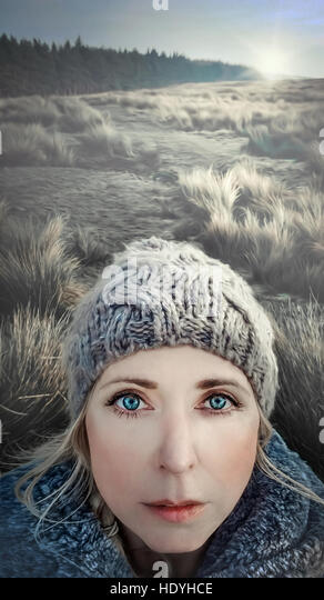 portrait of the young woman standing in snowy meadow - Stock Image