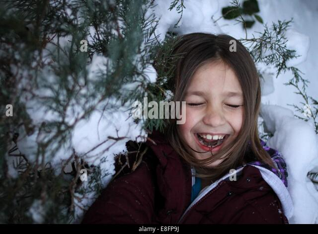 Girl standing by snow covered trees laughing - Stock Image