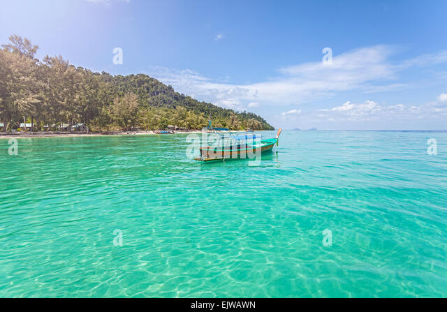 Little boat by tropical island, perfect vacation concept. - Stock Image