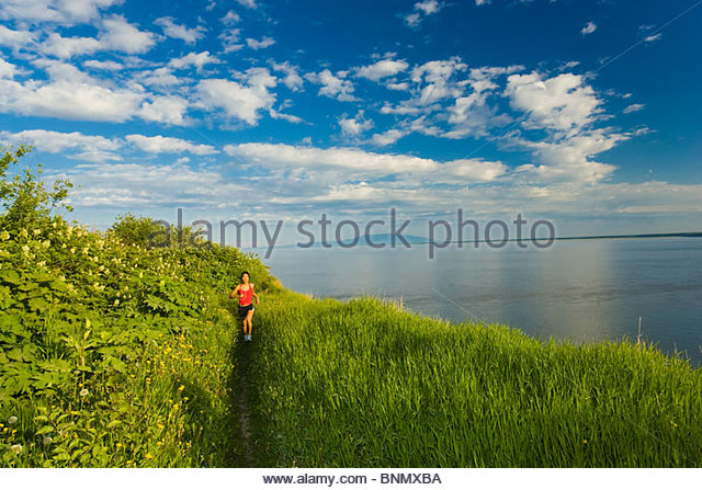 Woman jogging along the coastal trail overlooking Cook Inlet near Anchorage in Southcental Alaska - Stock Image