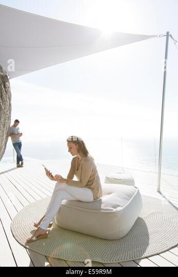 Woman using digital tablet on modern balcony - Stock Image