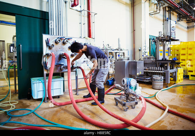 Man working in a brewery, connecting hoses to a metal beer tank. - Stock Image