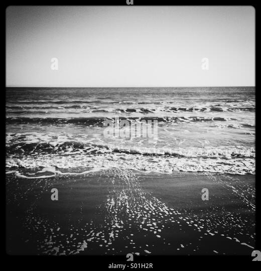 Black and white photograph of the shore as waves pull back from the sand - Stock Image