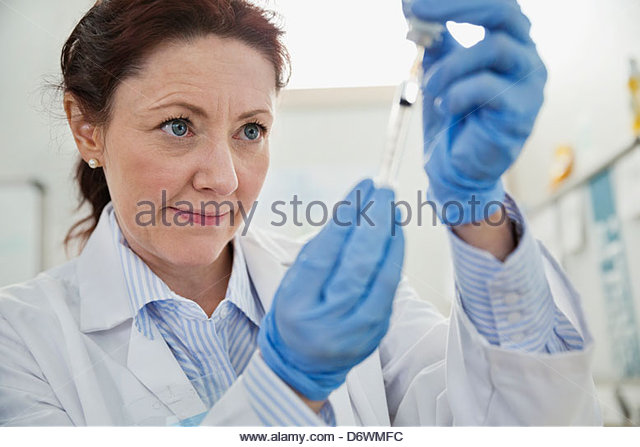 Mature female doctor filling syringe - Stock Image