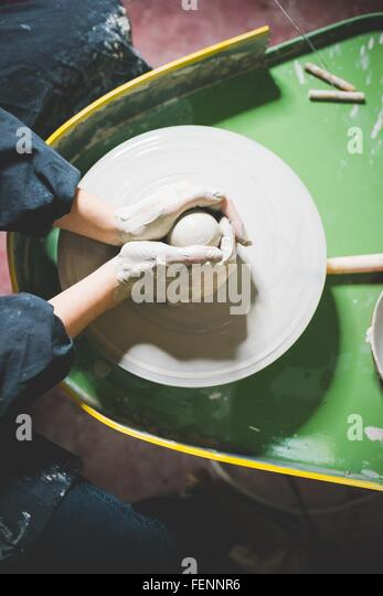 Overhead view of young womans hands shaping clay on pottery wheel - Stock Image