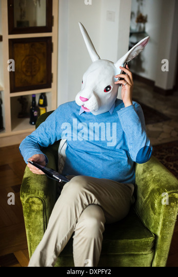 elegant business multitasking rabbit mask man using devices at home - Stock Image