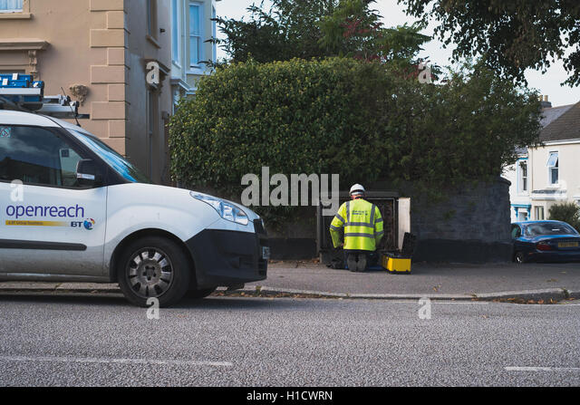 A BT Openreach engineer working at roadside equipment cabinet installing broadband - Stock Image