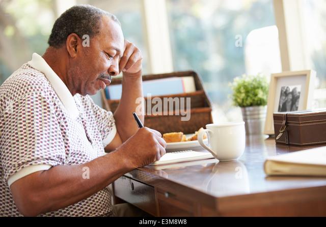 Senior Man Writing Memoirs In Book Sitting At Desk - Stock Image