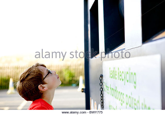 A young boy looking at a recycling container for textiles - Stock Image