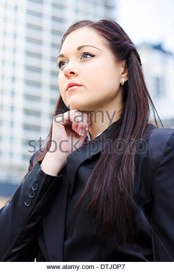 Half Body Portrait Of A Young Business Woman Standing Is The City Center Holding Hand To Head In An Expression Of - Stock Image