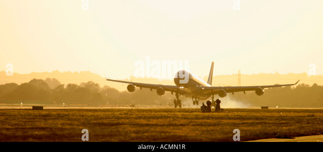 Large commercial airliner landing at dusk - Stock Image