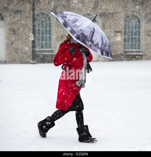 A woman walking through snow in Victoria Square, Birmingham, UK. The umbrella depicts the Houses of Parliament in - Stock-Bilder