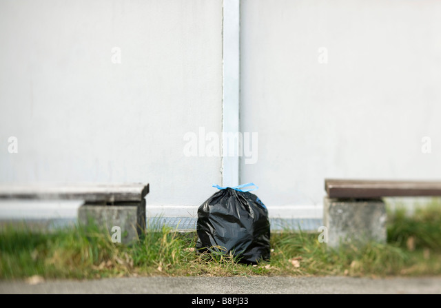 Garbage bag sitting on ground between two benches - Stock Image