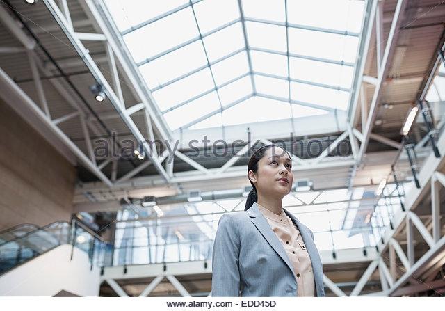 Confident businesswoman in atrium - Stock Image