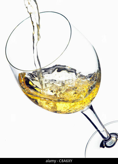 Pouring white wine into a glass - Stock Image
