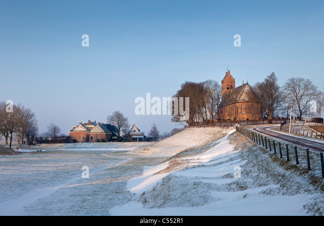The Netherlands, Hogebeintum, Church on mound in snow. - Stock Image