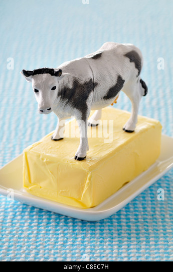 Platic cow on a slab of butter - Stock Image