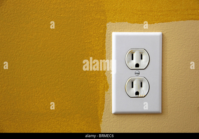 US plug in the wall with yellow paint around it. - Stock Image
