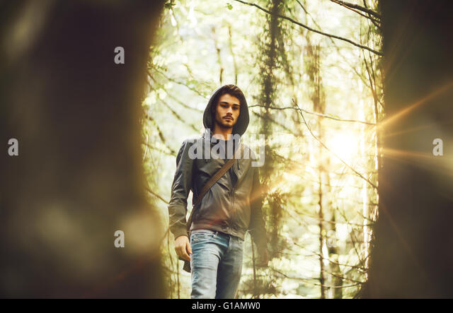 Young man walking in the forest framed by trees - Stock Image