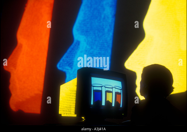 designer working on computer  with multiple images on large screen - Stock Image