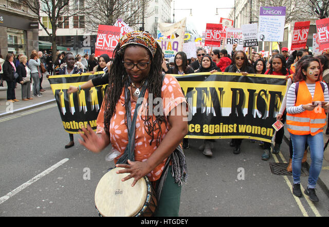 London, UK. March 11, 2017:  A protestor drums as she marches on Oxford Street on the 10th annual Million Women - Stock Image