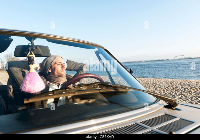 Germany, Hamburg, Man sitting in classic cabriolet car near Elbe riverside - Stock Image