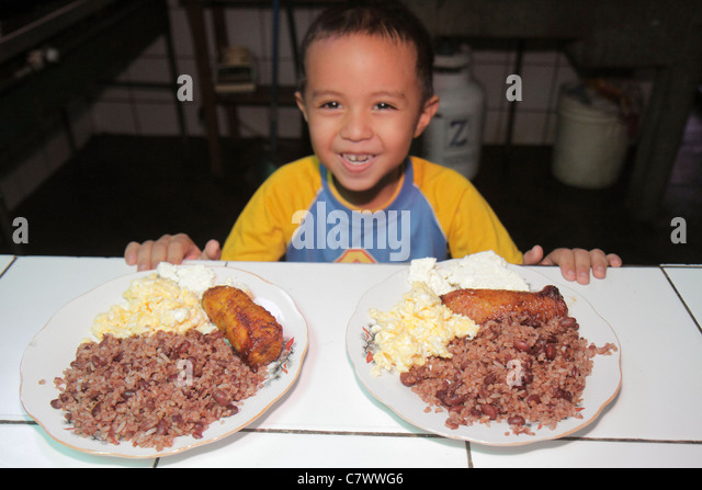 Managua Nicaragua Hispanic boy preschooler food plate typical food rice beans scrambled eggs fried plantain portion - Stock Image
