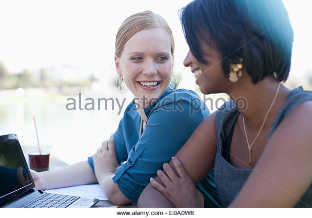 Businesswomen working on laptop in park - Stock Image