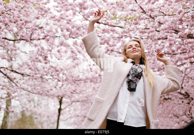 Young woman arms raised enjoying the fresh air in spring park. Carefree young female at spring blossom garden - - Stock Image