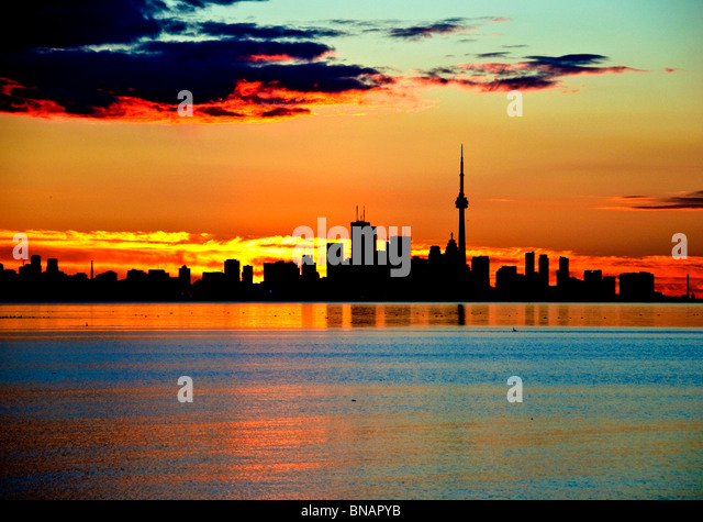 early morning view of toronto skyline with glowing orange sky - Stock Image