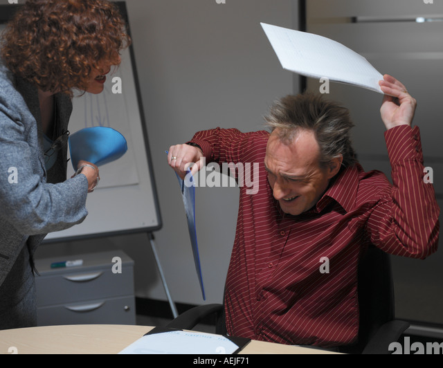 40 s woman shouting at 40 s man in office - Stock Image