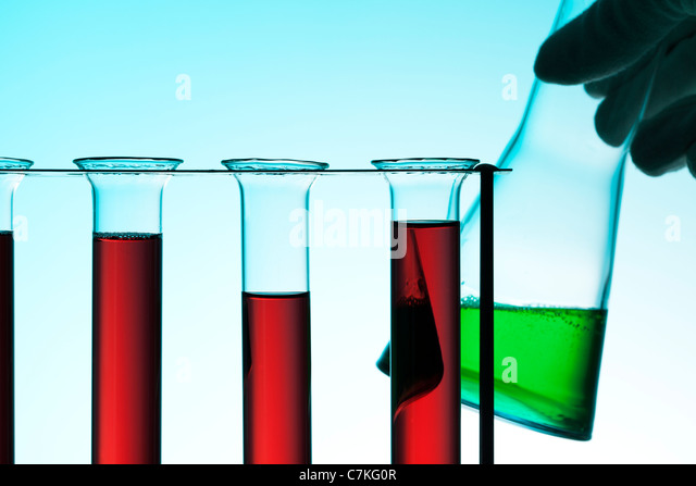 chemical laboratory scene, test tubes in rack with red liquid, hand holding Erlenmeyer flask with green liquid - Stock Image